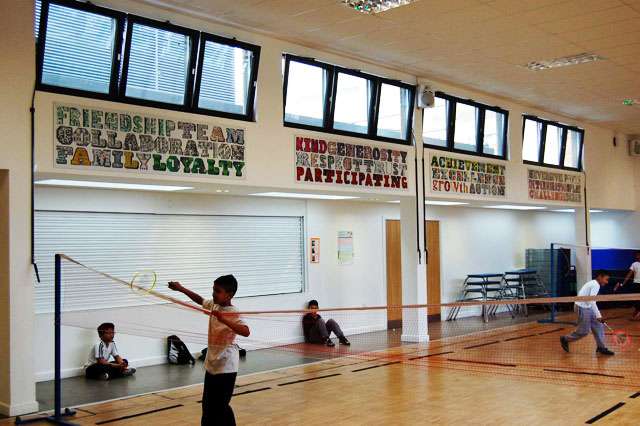 Lettering on the walls in the school hall with the children playing sport